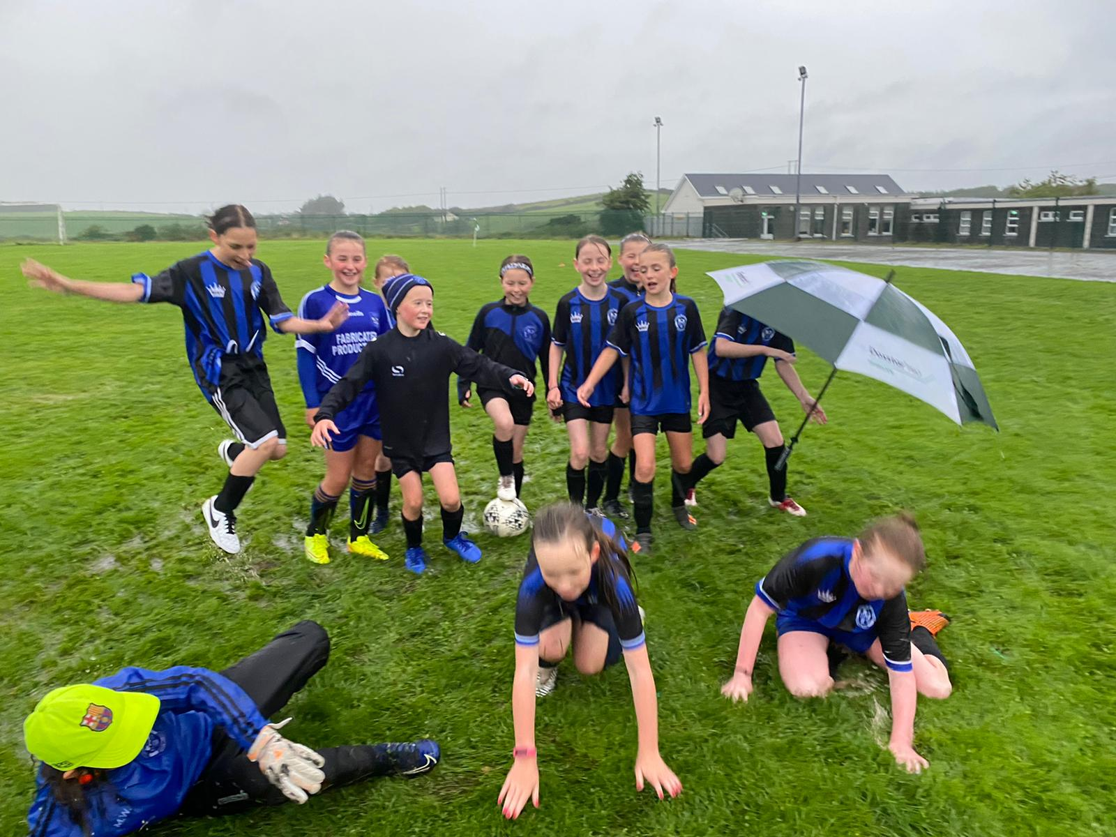 Our Under 12 girls team put up a very entertaining performance in near apocalyptic conditions in against Connolly at Kilmaley NS. There was great determination on show by the girls. We had a young team in comparison to our opponents but matched them fully. While our supporters stayed dry in their cars, our intrepid management and team stayed out together in a monsoon sponsored by generously donated umbrellas from the head of the Drumline primary teachers association.